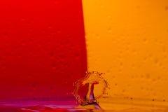 As gotas, pulverizam, espirram da água em um fundo colorido Imagem de Stock