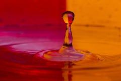 As gotas, pulverizam, espirram da água em um fundo colorido Imagens de Stock Royalty Free