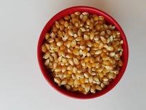 As grões inteiras estudam - a bacia de núcleos de milho unpopped na bacia vermelha, vista de diretamente acima, e no close up, la imagens de stock royalty free