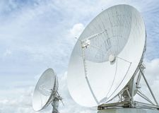 As grandes antenas parabólicas brancas gerenciem acima em direção ao céu no céu azul fotografia de stock