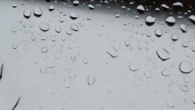 As grandes e gotas pequenas da água no vidro surgem filme
