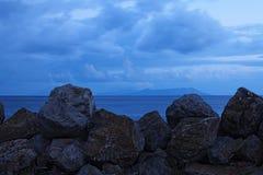 As grandes pedras são projetadas proteger o litoral das grandes ondas As ilhas podem ser vistas no horizonte Marina di Patti Sici Fotos de Stock