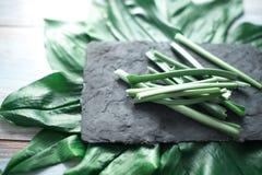 As hastes verdes cortadas em uma cozinha preta embarcam Foto de Stock