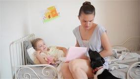 As histórias novas do tempo da cama da leitura da mãe à criança, cão pequeno vêm ao mum e afaga o seu video estoque