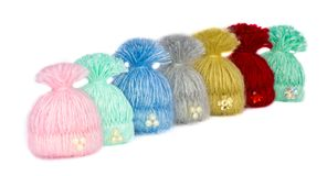 Seven beautiful multi-colored caps - handmade brooches lined up stock photo