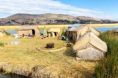 As ilhas de flutuação no lago Titicaca Puno, Peru, Ámérica do Sul, cobriram com sapê em casa Fotografia de Stock Royalty Free
