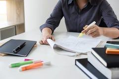 As imagens de estudar o estudante entregam a escrita no livro durante a leitura fotografia de stock