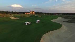 As imagens de vídeo aéreas de dois carrinhos de golfe com povos montam em um campo de golfe no por do sol video estoque
