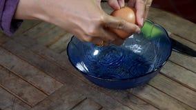 As imagens de vídeo, shell de ovo da mão que quebra com faca de aço inoxidável e deixam-na cair então na bacia de vidro azul filme