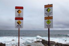 As images gráficas de advertência do oceano 'ressaca alta ''repentina deixam cair ''ondas partem rochas 'escorregadiços 'na borda fotografia de stock royalty free