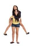As irmãs andam às cavalitas sobre Fotos de Stock Royalty Free