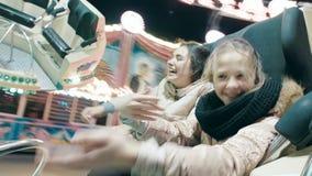 As irmãs bonitas montam uma atração de giro em um parque de diversões As jovens mulheres estão dançando em uma atração filme