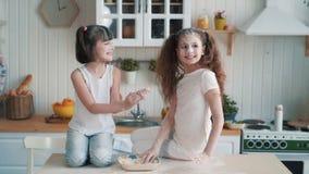 As irmãs bonitos que jogam a farinha em se, têm o tempo na cozinha, movimento lento do divertimento