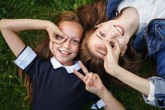 As irmãs encontram-se no gramado verde fotografia de stock royalty free