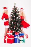 As irmãs felizes bonitas juntam perto da árvore e dos presentes de Natal imagem de stock