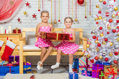 As irmãs felizes que guardam um presente vermelho grande e sentam-se em um banco em um ajuste do Natal Fotos de Stock