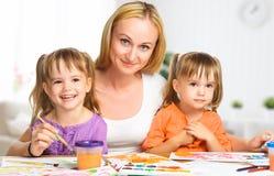 As irmãs gêmeas das crianças tiram pinturas com sua mãe no kindergarte Fotos de Stock