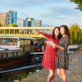 As irmãs gêmeas no às bolinhas vermelho e preto vestem-se usando o mapa perto do rio Seine em Paris, França imagens de stock royalty free