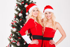 As irmãs juntam nos trajes de Papai Noel que estão a árvore de Natal próxima foto de stock