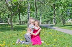 As irmãs mais nova felizes bonitos abraçam-se com ternura fotografia de stock royalty free