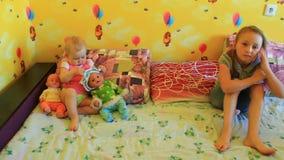 As irmãs mais nova jogam com suas bonecas na sala video estoque