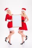 As irmãs novas encantadores juntam com a placa vazia que mostra os polegares acima imagem de stock royalty free