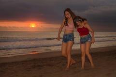 As irmãs novas ou a menina chinesa asiática na praia do por do sol com seu melhor amigo que tem o divertimento que apreciam féria imagens de stock
