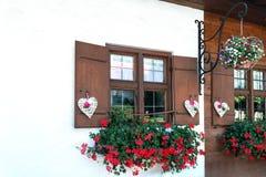 As janelas da casa de madeira são decoradas belamente com corações e as flores brancos fotografia de stock