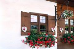 As janelas da casa de madeira são decoradas belamente com corações e as flores brancos imagens de stock