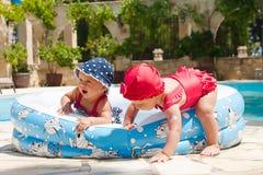 As jovens crianças felizes estão jogando fora em uma piscina do bebê Imagem de Stock