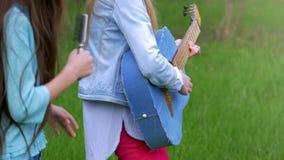 As jovens crianças que as amigas se divertem cantam músicas e dança junto jogando a guitarra tenha a natureza do divertimento vídeos de arquivo
