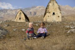 As jovens crianças sentam-se na grama seca no fundo das montanhas e de construções ossetos antigas fotografia de stock