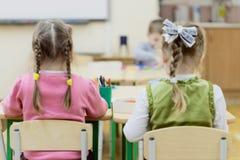 As jovens crianças sentam-se no jardim de infância na tabela contratada, tiram, aprendem no berçário fotografia de stock