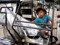 As jovens crianças montam um triciclo no assento do ` s do motorista Fotografia de Stock Royalty Free