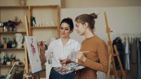 As jovens mulheres alegres professor e estudante estão discutindo a arte finala junto que falam e que olham a imagem Oficina mode vídeos de arquivo