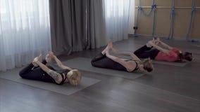 As jovens mulheres aprendem asanas da ioga a fim tornar-se mais flexíveis e plásticas filme