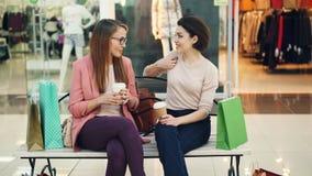 As jovens mulheres bonitas estão conversando no shopping que guarda as bebidas afastadas que sentam-se no banco com posição dos s vídeos de arquivo