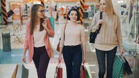 As jovens mulheres bonitas estão falando ao andar em uns sacos de papel levando do shopping com compras Varejo, feliz filme