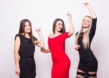 As jovens mulheres bonitas têm o divertimento nos vestidos da noite que levantam sobre o branco Foto de Stock