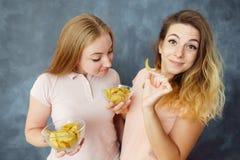 As jovens mulheres bonitos apreciam comer microplaquetas de batata fotografia de stock