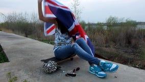 As jovens mulheres com Union Jack embandeiram o assento com seu skate na pista do cimento fora video estoque