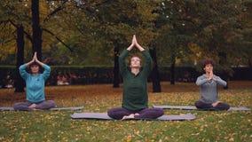 As jovens mulheres de Spititual estão meditando o assento na posição dos lótus sobre esteiras da ioga no parque e no ar fresco de vídeos de arquivo
