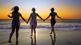 As jovens mulheres e duas meninas correm fora da água do oceano no por do sol na praia tropical Foto de Stock Royalty Free