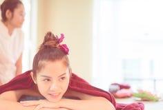 As jovens mulheres estão encontrando-se em uma cama dos termas Fotografia de Stock