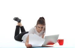 As jovens mulheres estão sentando-se no fundo branco com portátil, copo, livros e papéis A menina do estudante que estuda, freela Imagens de Stock Royalty Free