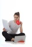As jovens mulheres estão sentando-se no fundo branco com portátil, copo, livros e papéis A menina do estudante que estuda, freela Foto de Stock Royalty Free