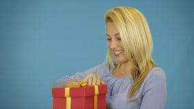 As jovens mulheres felizes tomam o presente A menina loura feliz genred a caixa de presente com a fita da curva do ouro Cara do s video estoque