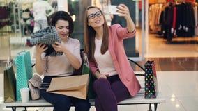 As jovens mulheres modernas estão usando o smartphone para fazer a chamada video em linha do shopping As meninas estão conversand video estoque