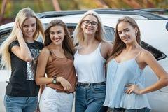 As jovens mulheres que estão perto do carro Fotos de Stock Royalty Free