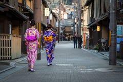 As jovens mulheres que vestem o quimono japonês tradicional andam na rua de Gion Fotografia de Stock Royalty Free